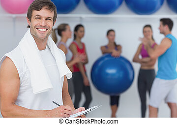 Trainer holding clipboard with fitness class in background