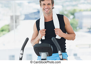 Smiling man working out at spinning class in bright gym -...
