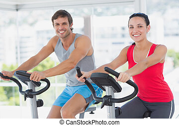 Smiling young couple working out at spinning class in a...
