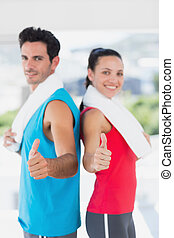 Fit couple gesturing thumbs up in bright exercise room -...