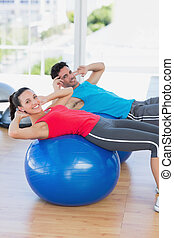 Fit young couple exercising on fitness balls at gym - Side...