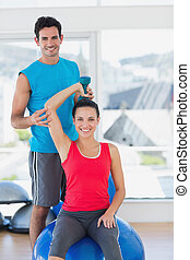 Male trainer helping woman with her exercises at gym