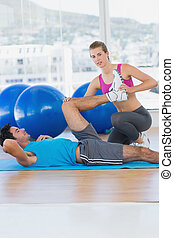Female trainer helping man with his exercises at gym - Side...
