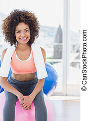 Fit young woman sitting on fitness ball at gym - Portrait of...