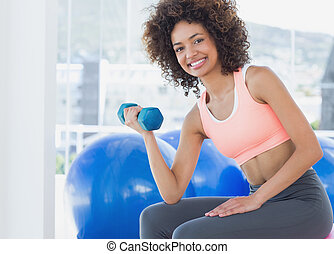 Smiling young woman exercising with dumbbell in gym -...