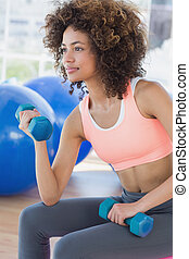 Young woman exercising with dumbbells in gym - Side view of...