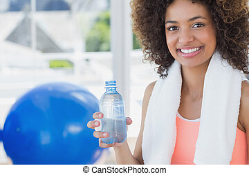 Fit young female holding water bottle at gym - Portrait of a...