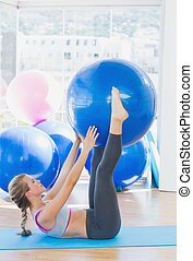 Side view of a sporty young woman holding exercise ball...