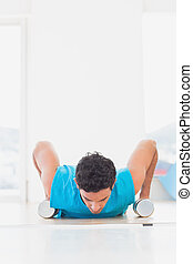 Man doing push ups with dumbbells in fitness studio