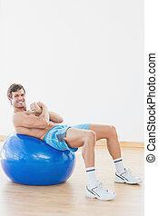 Shirtless man exercising on fitness ball in gym