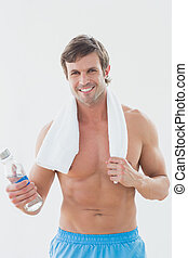 Portrait of a smiling shirtless man holding water bottle