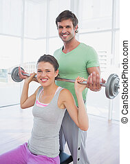 Instructor helping fit woman to lift barbell in gym