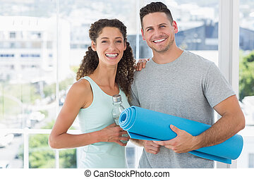Happy couple holding water bottle and exercise mat at gym -...