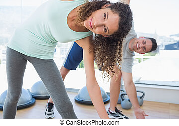 Woman with man doing stretching exercise - Portrait of fit...