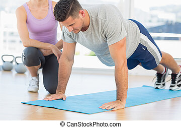 Trainer assisting man with push ups - Female trainer...