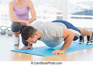 Trainer helping man with push ups - Female trainer helping...
