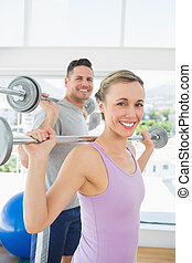 Woman lifting weights in fitness club