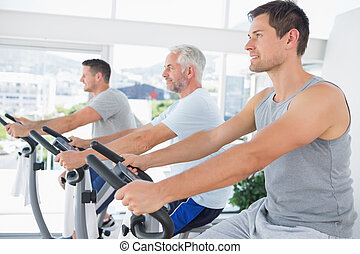 Men working out on exercise machine - Row of men working out...