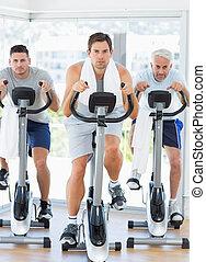 Men using exercise bikes - Full length of men using exercise...