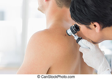 Doctor examining mole on back of man - Female doctor...