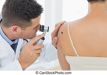 Doctor examining mole on back of woman - Male doctor...