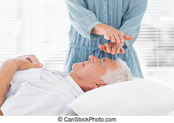 Massage therapist performing Reiki over man - Massage...