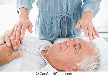 Man having Reiki treatment by therapist - Senior man having...