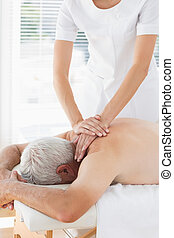 Physiotherapist massaging back of patient - Female...