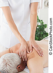 Massage therapist massaging back of senior man - Female...