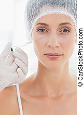 Attractive woman having botox injection - Closeup portrait...
