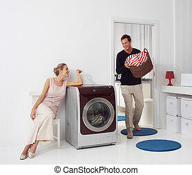 woman and man doing laundry - Housework, young woman and man...