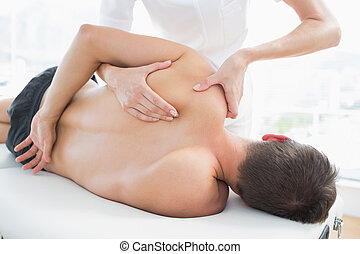 Physiotherapist giving shoulder massage to man -...