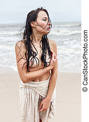 seminude woman on the cold sea beach - Beautiful young...
