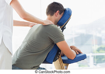 Physiotherapist giving shoulder massage to man - Female...