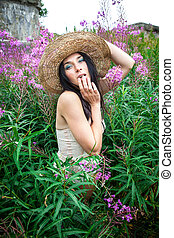girl in straw hat against nature and old wall background -...