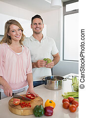 Couple cooking vegetables in kitchen - Portrait of happy...