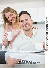 Couple with coffee mugs and newspaper in kitchen - Portrait...