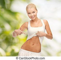 beautiful sporty woman pointing at her abs