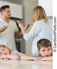 Sad children leaning on table while parents arguing