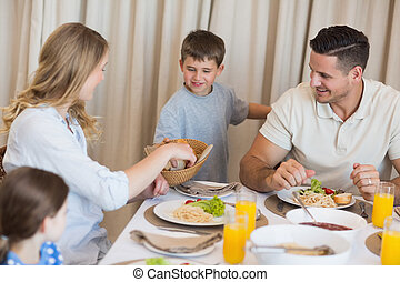 Family eating lunch at dining table - Happy family eating...