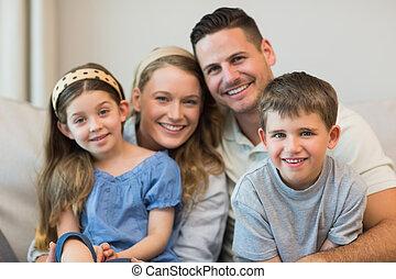 Parents and children sitting on sofa - Portrait of parents...
