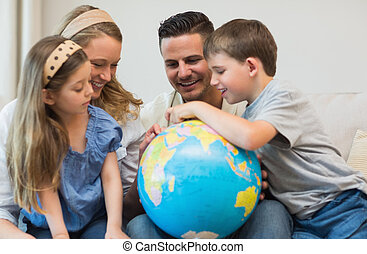 Family searching places on globe - Happy family of four...