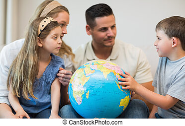 Family with globe in house - Family with globe looking at...