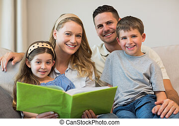 Family with photo album sitting on sofa - Happy family with...