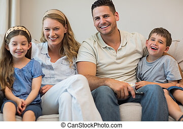 Happy parents and children sitting on sofa - Portrait of...