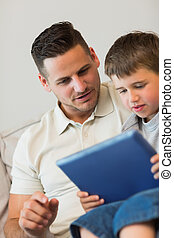 Father and son using tablet computer on sofa at home