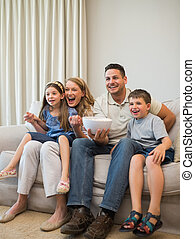 Excited family watching television on sofa - Full length of...