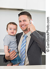 Businessman carrying baby boy while on call - Portrait of...