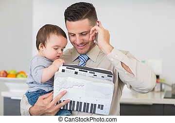 Businessman with documents carrying baby while on call -...