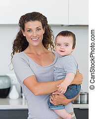 Portrait of happy mother and baby boy in kitchen at home